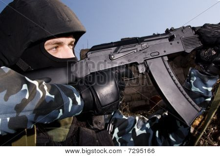 Soldier Shooting With Automatic Rifle From The Hideout