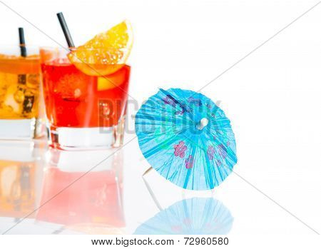 Two Cocktail With Orange Slice On Top Isolated Behind Blue Umbrella On White Background