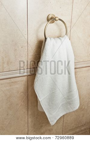 white hand towel on metallic hanger. Close up background of a bathroom hand towel on tile wall.