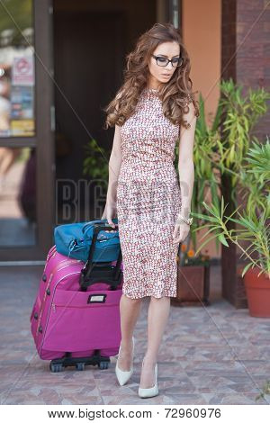Beautiful woman with suitcases leaving the hotel in a big city. Attractive redhead with sunglasses