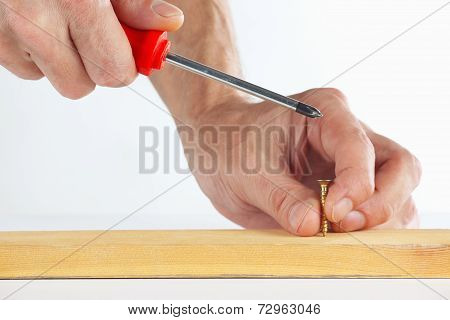 The hand of the worker tightening the screw in a wooden block