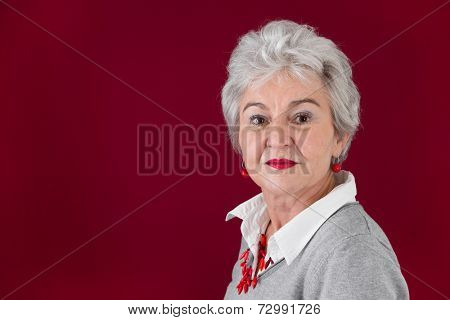 Portrait of elderly woman on red background.