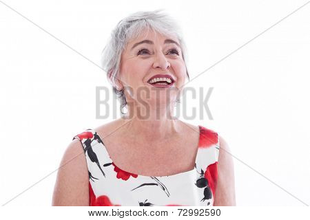 Isolated portrait of happy senior woman in summer dress over white background.
