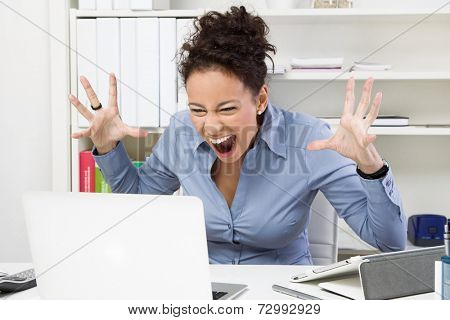 Angry woman with computer at workplace - bad message.
