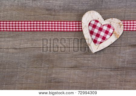 Top view of red checked heart decoration on wooden background - country style