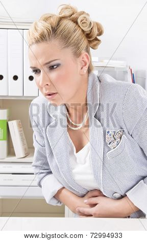 Young blond woman sitting in office with aching stomach