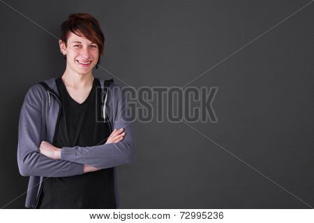 Studio shot of young boy with arms crossed