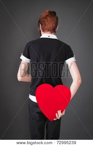 Rear view of boy holding heart behind his back