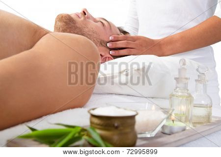 Young man getting scalp massage and relaxing