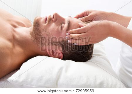 Side view of young relaxed man getting scalp massage