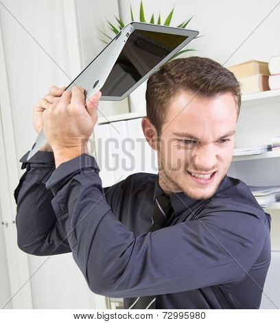 Close up of furious businessman throwing his laptop away