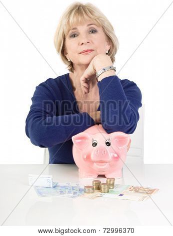 Unhappy senior woman sitting and leaning on a pink piggy bank, isolated on white background
