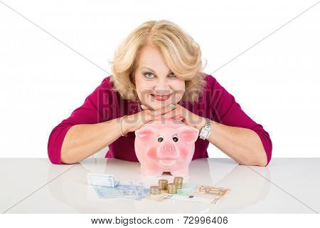Happy senior woman leaning on pink piggy bank, isolated on white background