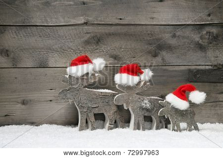 Funny christmas card with three elks wearing a santa hat for a greetings on a wooden background with snow