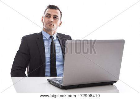 Attractive business man sitting at desk with laptop thinking isolated on white background