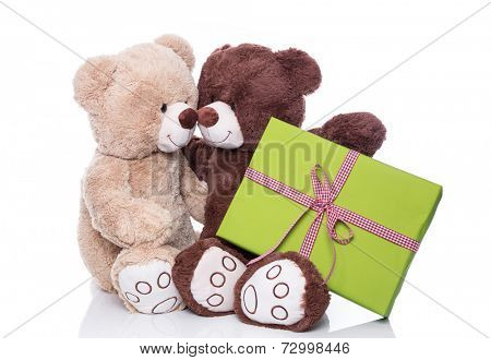 Christmas: Two isolated teddy bears in love holding a green present