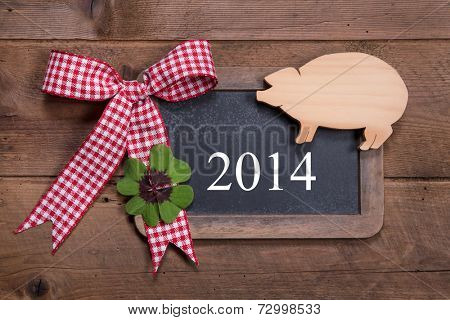 Happy new year 2014 - greeting card on a wooden background with a lucky pig and a green clover with a red checked ribbon