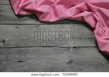 Checkered fabric as border on grey wooden background for christmas, birthday, publicity, mother's day, valentine's day or a advertising, board