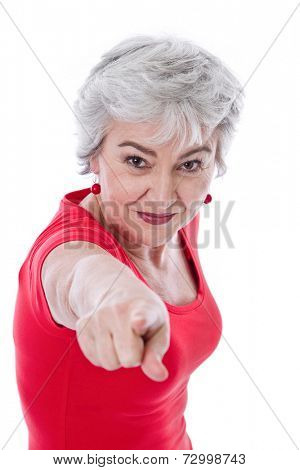 Confident woman with grey hair dressed in red pointing at camera isolated on white background