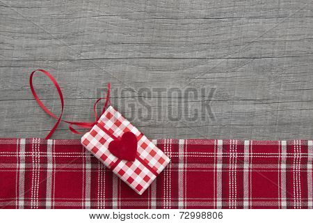 Present for christmas, valentine's day, birthday, mother's day in Country style on a wooden shabby chic background in red and green checkered with a heart