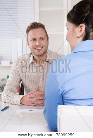 Consultant - business man sitting at desk listening to a business woman or customer