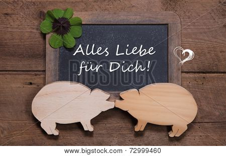 Greeting card with clover and two wooden pigs - like a couple - luck for new years day, valentine's day or birthday - love - on a old rustic chalkboard