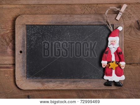 Chalk board for Merry Christmas message, santa on wooden background for a greeting card - country style - old slate sign - text