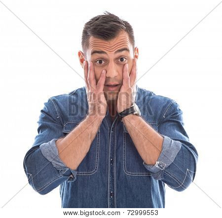 Shocked: young man in blue denim shirt with hands touching face isolated on white background