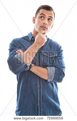 Thinking: young doubtful man in blue denim shirt isolated on white background