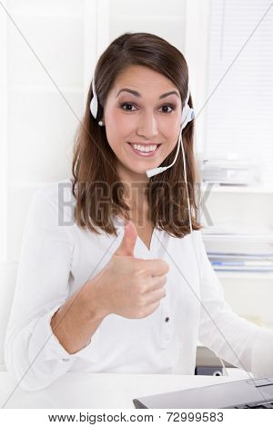 Pretty businesswoman with headset sitting at desk with giving thumbs up in white clothes - at the doctor