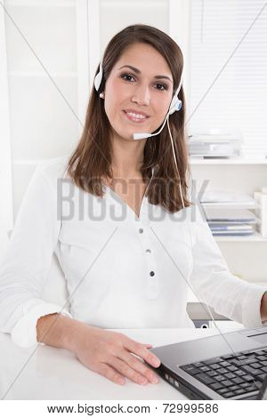 Pretty businesswoman in white sitting at helpdesk and laptop with headset