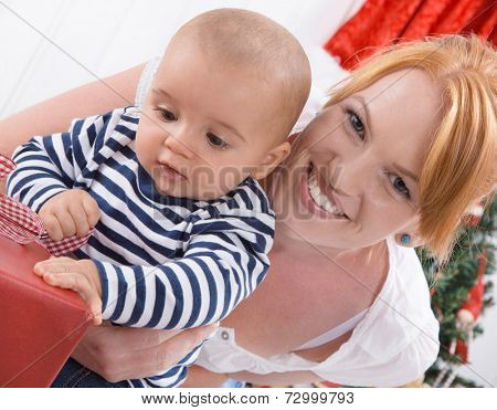 Unconditional love - mother and baby opening a Christmas or birthday present