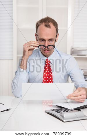 Short sighted at work - balding businessman looking through glasses at document