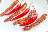 foto of bacon strips  - Fried Bacon Strips With Chili Pepper On The Square Plate - JPG