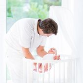 foto of bassinet  - Young Smiling Father Putting His Newborn Baby In A White Round Crib Standing At A Big Window - JPG