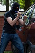 pic of plunder  - Criminal smashing a glass and breaking into a car - JPG