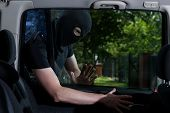 image of plunder  - Thief with obscured face open car lock - JPG