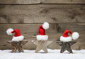 stock photo of handicrafts  - Three wooden stars with santa hats on wooden background  - JPG