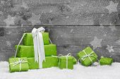 picture of coupon  - Green Christmas presents with snow on grey wooden background for a greeting card or coupon - JPG