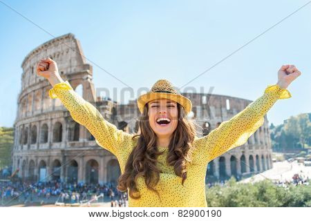 Portrait Of Happy Young Woman Rejoicing In Front Of Colosseum In