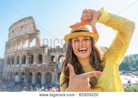 Happy Young Woman Framing In Front Of Colosseum In Rome, Italy