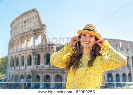 Portrait Of Happy Young Woman With Audio Guide In Front Of Colos