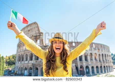 Portrait Of Happy Young Woman Rejoicing With Italian Flag In Front Of Colosseum In Rome, Italy