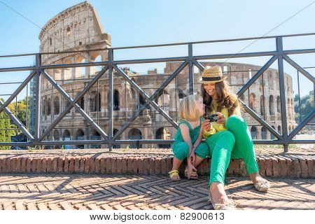 Mother And Baby Girl Sitting In Front Of Colosseum In Rome, Italy