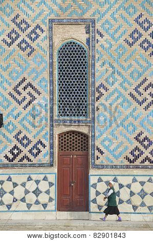 Woman passes by the wall of the mausoleum of Khoja Ahmed Yassawi in Turkistan, Kazakhstan.