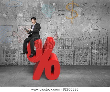 Using Tablet Businessman Sitting On Red Percentage Sign With Doodles