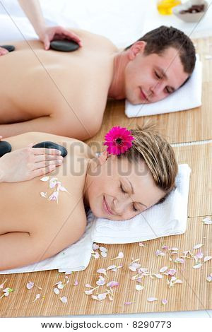 Young Couple Enjoying A Back Massage With Stone