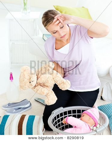 Exhausted Young Woman Putting Toys Into A Basket