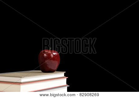 Stack Of Books With Red Apple And Blackboard