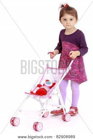 funny little girl rolls the stroller.
